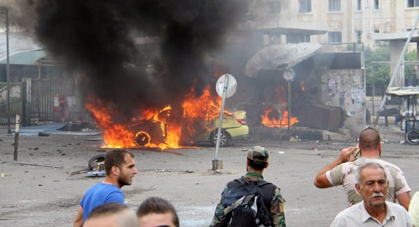 A Syrian army soldier and civilians inspect the damage after explosions hit the Syrian city of TartusReuters
