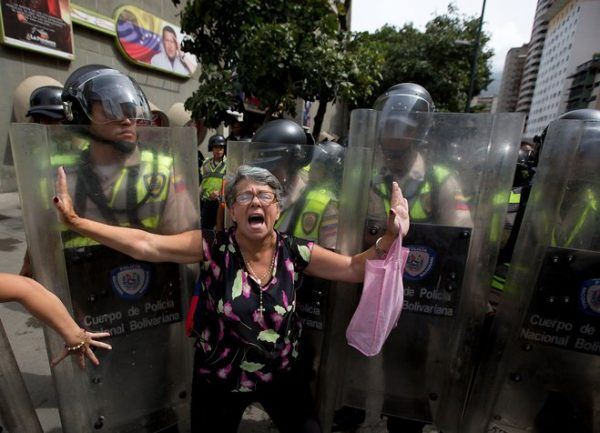 An angry demonstrator is blocked by Bolivarian National police during an anti-government march to the headquarters of the national electoral body, CNE, in Caracas, Venezuela, Wednesday, May 18, 2016. Opposition protesters were blocked from reaching the CNE as they demand the government allow it to pursue a recall referendum against Venezuela's President Nicolas Maduro. (AP Photo/Fernando Llano)