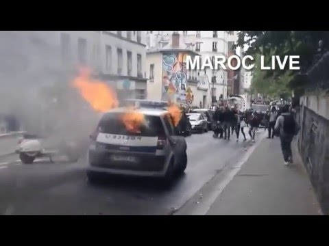 A video has emerged of the shocking moment protesters attacked and set on fire a police car in central Paris on Tuesday, forcing the two officers inside to flee the vehicle as it burst into flames.