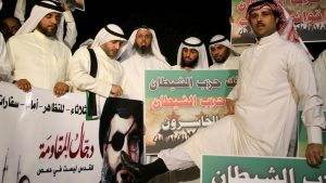 Kuwaiti protesters hold placards against Lebanese Shiite movement Hezbollah's chief Hassan Nasrallah (portrait) during a protest in front the Lebanese embassy against Hezbollah's and Iran's involvement in Syria, in Kuwait city on June 11,2013. (AFP)