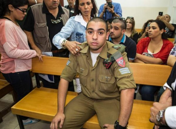 Israeli soldier Elor Azaria, who was caught on video shooting a wounded Palestinian assailant in the head as he lay on the ground, sits during a hearing at a military appeals court in Tel Aviv during which he was charged with manslaughter. (JACK GUEZ/AFP/GETTY IMAGES)