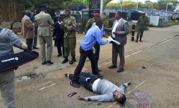 Kenyan security forces stand next to the body of a man who was killed outside the U.S. Embassy in Nairobi, Kenya Thursday, Oct. 27, 2016. A Kenyan police official said the man was shot dead after stabbing a policeman guarding the perimeter wall of the U.S. Embassy in Nairobi. (AP Photo)