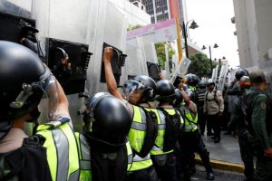 Riot police officers rise their shields as they escort people walking out from the National Assembly after a session in Caracas, Venezuela October 27, 2016. REUTERS/Carlos Garcia Rawlins