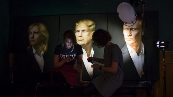 Two women wait in front of portraits of French Front National leader Marine Le Pen, US President-elect Donald Trump and Russian President Vladimir Putin for a live telecast of election results in a pub in Moscow. Photo: AP