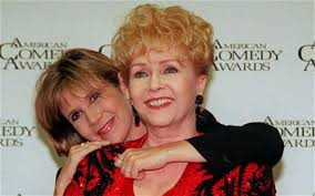 Debbie Reynolds is hugged by her daughter Carrie Fisher