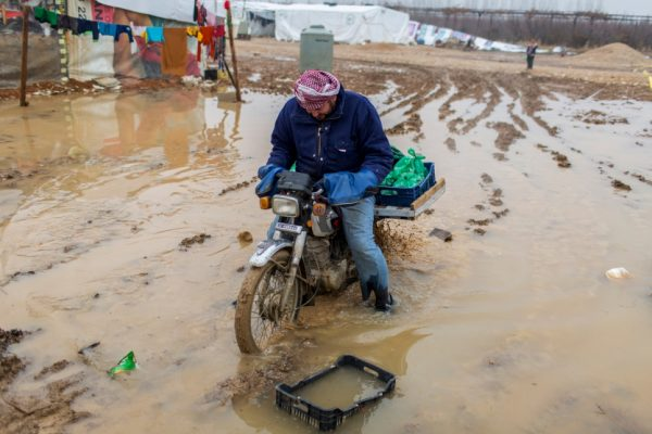 A Syrian refugee rides a motorbike through deep mud at the informal Tal Sarhoun settlement in the Bekaa Valley, Lebanon.   © UNHCR/Diego Ibarra Sánchez