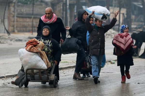 A man pushes a woman on a cart as they flee deeper with others into the remaining rebel-held areas of Aleppo, Syria. REUTERS/Abdalrhman Ismail