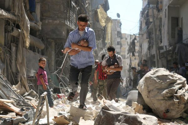 Syrian men carrying babies make their way through the rubble of destroyed buildings following a reported air strike on the rebel-held Salihin neighborhood of the northern city of Aleppo, on September 11. AMEER ALHALBI/AFP/GETTY