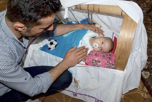 "Hassan Jamil, a Kurdish peshmerga fighter, is seen with his infant son, Trump Jamil Hassan — a.k.a. ""Little Trump"" — in his living room in Chrra, Iraq. (Washington Post/Peter Holley)"
