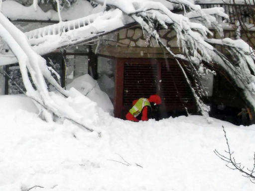 A rescue clears snow in front of the Rigopiano Hotel, following an avalanche in Farindola, Italy, early Thursday, Jan. 19, 2017. Rescue workers were met with an eerie silence Thursday when they reached a four-star spa hotel struck by an avalanche in a mountainous earthquake-stricken region of central Italy. At least 30 people were missing, including at least two children, authorities said. (Corpo Nazionale Soccorso Alpino e Speleologico/The National Alpine Cliff and Cave Rescue Corps (CNSAS) via AP)