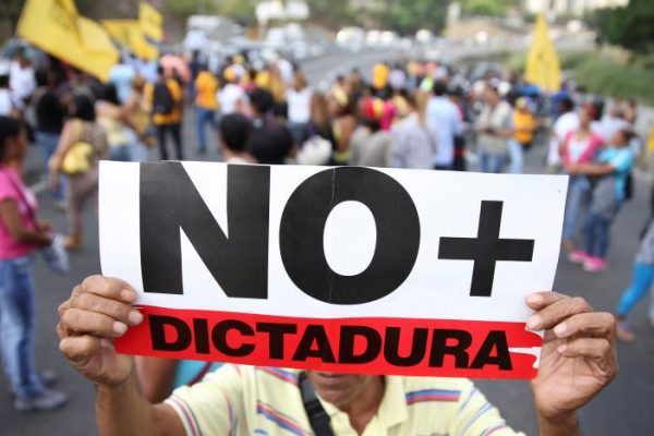 """Opposition supporters holding a placard that reads, """"No more dictatorship"""" shout slogans as they block a highway during a protest against Venezuelan President Nicolas Maduro's government in Caracas, Venezuela March 31, 2017. REUTERS/Carlos Garcia Rawlins"""