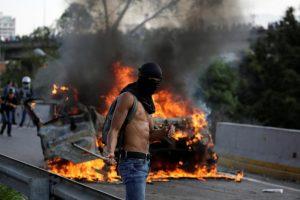 A demonstrator stands near fire during a rally against Venezuela's President Nicolas Maduro in Caracas. REUTERS/Carlos Garcia Rawlins