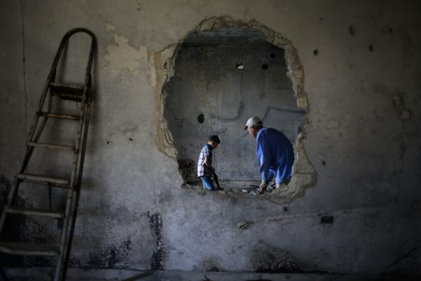 A Syrian man and his son clean their house in the mountain resort town of Zabadani in the Damascus countryside, Syria, Thursday, May 18, 2017. (AP Photo/Hassan Ammar)