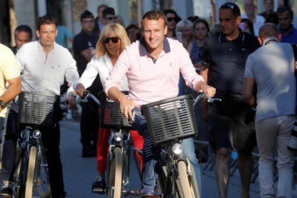 French President Emmanuel Macron and his wife Brigitte Trogneux ride their bicycles as they leave their home in Le Touquet, France June 17, 2017. REUTERS/Philippe Wojazer