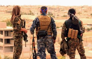 FILE - This April 30, 2017, file photo provided by the Syrian Democratic Forces (SDF) shows fighters from the SDF looking toward the northern town of Tabqa, Syria.