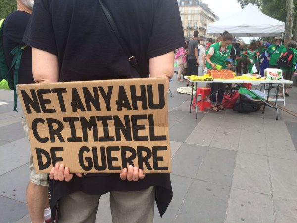 "A demonstrator holds a sign that says ""Netanyahu is a war criminal"" at a protest in Paris, July 15 2017."