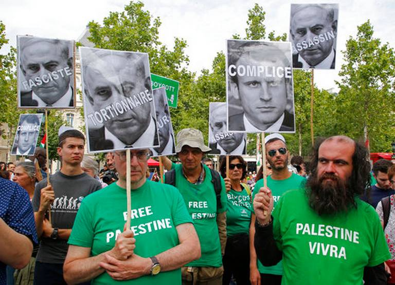 Pro-Palestinian activists hold pictures of Israeli Prime Minister Benjamin Netanyahu and French President Emmanuel Macron as they gather to protest Israeli Prime Minister's visit to France in Paris, Saturday, July 15, 2017. French President Emanuel Macron's invited on Sunday Israeli Prime Minister Benjamin Netanyahu for bilateral talks and a commemoration of a mass deportation of French Jews to Nazi camps 75 years ago. Placards read from left, fascist, torture, partner in crime and killer. Michel Euler AP Photo
