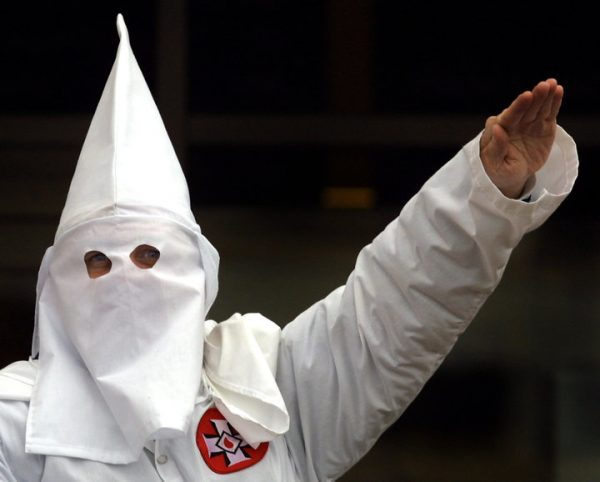 "A Klansman raises his left arm during a ""white power"" chant at a Ku Klux Klan rally . KKK worked very hard in 2016  to get Donald Trump elected as US president"