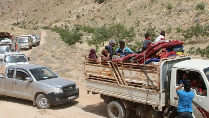 Syrian refugees ride vehicles in the Lebanese eastern border town of Arsal. Lebanon hosts 1.5m people who have fled Syria's six-year war © AFP
