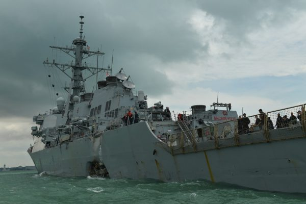 The United States Navy missile destroyer USS John S McCain displaying a hole in its hull as it is towed into the Changi Navy Base off the eastern coast of Singapore, Aug. 21 2017. (Desmond Foo/The Straits Times/Sph/EPA)