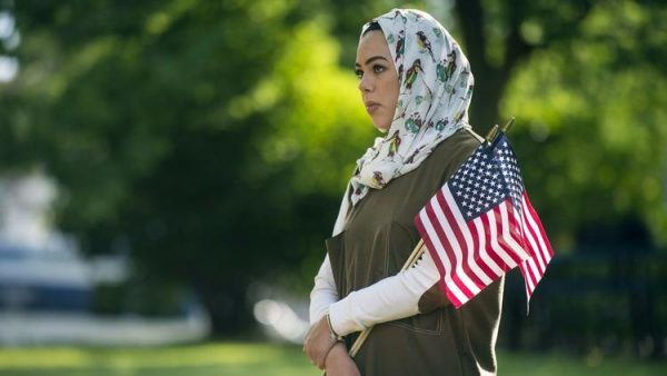 A Muslim woman holds American flags at an interfaith prayer service in Flint, Mich., on June 22. (Shannon Millard / Associated Press) American Muslims see Trump as unfriendly but find support from non-Muslim compatriots, survey shows