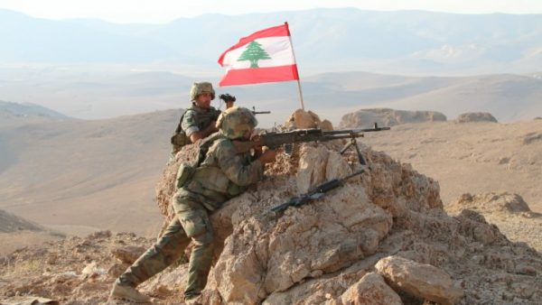 Lebanese army soldiers position  the Lebanese flag on top of a hill  in the town of Ras Baalbek that the army recaptured from ISIS , Lebanon August 21, 2017.
