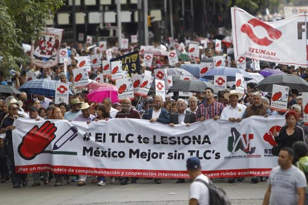 """Union workers and farmers protest as NAFTA renegotiation begins in Washington, D.C., in Mexico City, Mexico August 16, 2017. The placards read """" NAFTA hurts"""""""