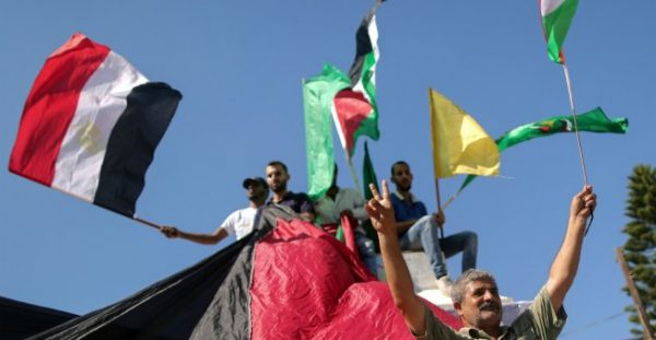 Palestinians wave the flags of Egypt, Palestine, Fatah and Hamas in Gaza City after rivals Hamas and Fatah reached a deal to end a decade-long split, on October 12, 2017