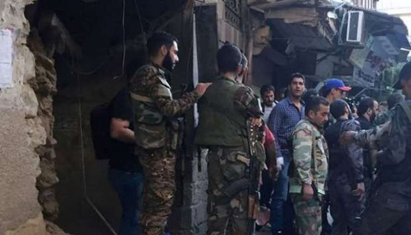 Syrian Army soldiers inspect the damaged site at the police HQ in central Damascus