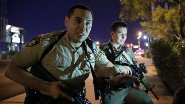 Police officers advise people to take cover near the scene of the mass shooting near the Mandalay Bay resort and casino on the Las Vegas Strip on Sunday, Oct. 1. Police said a 64-year-old gunman on the 32nd floor of the hotel rained down gunfire on thousands of concertgoers, killing at least 50. (AP Photo/John Locher)