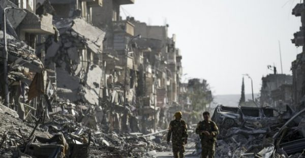 BULENT KILIC / AFP | Fighters of the Syrian Democratic Forces (SDF) walk down a street in Raqqa past destroyed vehicles and heavily damaged buildings on October 20, 2017.