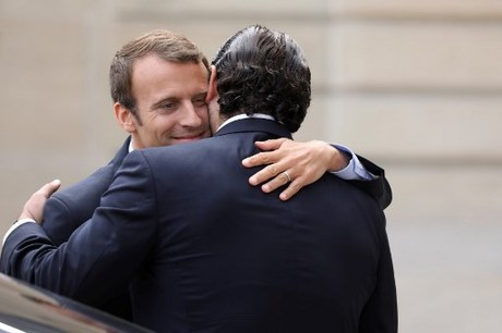 French President Emmanuel Macron (L) hugs Lebanese Prime Minister Saad Hariri after their meeting at the Elysee Palace in Paris on September 1, 2017. / AFP PHOTO / ludovic MARIN