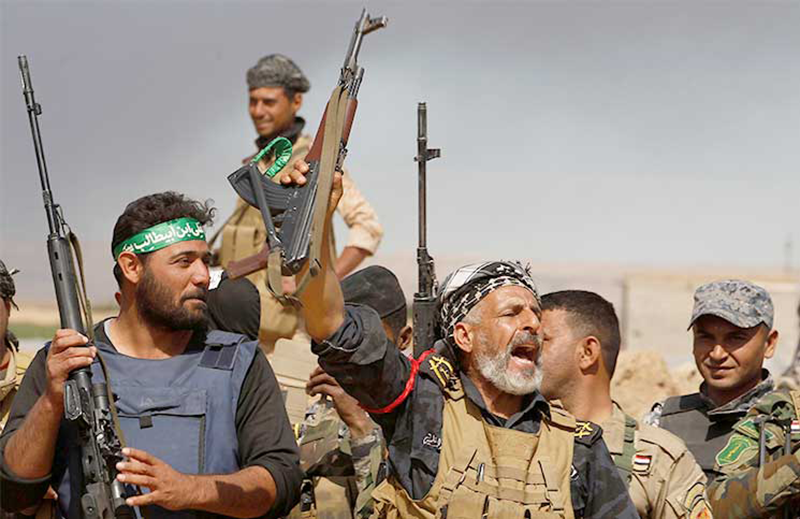 """Popular Mobilization Forces (PMF) (al-Hashd al-Shaabi) fighters. Iraqi-Shiite Grand Ayatollah Ali Sistani urged the Shiite armed groups to stay away from political participation and """"requested that all weapons come under government's control"""""""