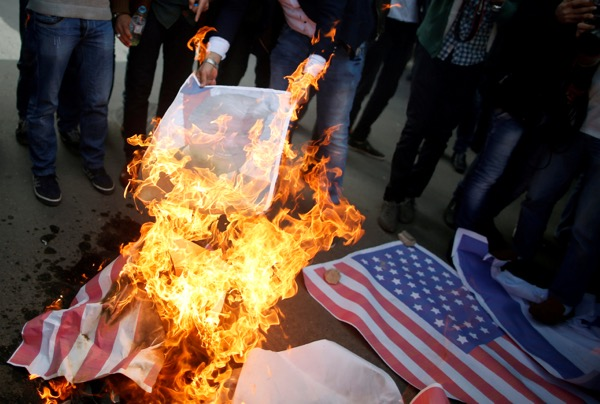 Palestinian protesters burn a poster depicting U.S. President Donald Trump and a representation of a U.S. flag during a protest against Trump's decision to recognize Jerusalem as the capital of Israel, in Gaza City December 7, 2017. REUTERS/Mohammed Salem