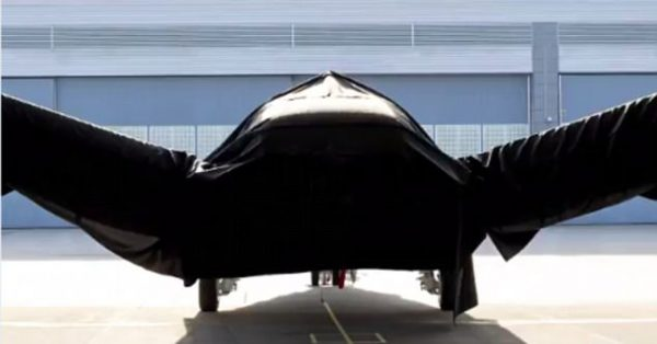 The craft, seen hidden under a black cover, is believed to be a radical new craft using electric 'hairdryer' to allow it to land and take off vertically.