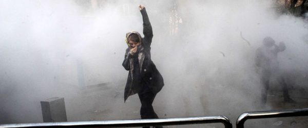 An Iranian woman raises her fist amid the smoke of tear gas at the University of Tehran during a protest driven by anger over economic problems, in the capital Tehran, Dec. 30, 2017.