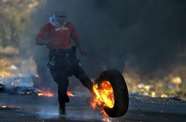 A Palestinian kicks a burning tire during clashes with Israeli troops at a protest against U.S. President Donald Trump's decision to recognize Jerusalem as Israel's capital, near the Jewish settlement of Beit El, near the West Bank city of Ramallah December 10, 2017. REUTERS/Mohamad Torokman