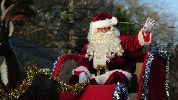 Santa waves to the crowds from his sleigh in the Cary Jaycees Christmas Parade, which took place on Saturday, December 12, 2015 in Cary, NC