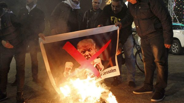 Palestinian protesters burn pictures of US President Donald Trump at the manger square in Bethlehem on December 5, 2017. © Musa Al Shaer / AFP