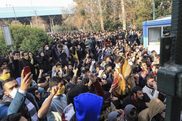 University students attend a protest inside Tehran University while a smoke grenade is thrown by anti-riot Iranian police, in Tehran, Iran, December 30,