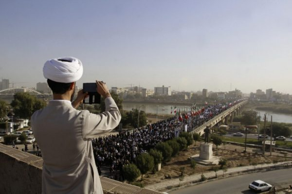 A clergyman takes a picture of a pro-government demonstration in the southwestern city of Ahvaz, Iran, Wednesday, Jan. 3, 2018. Iranian state media reported that pro-government demonstrations were once again held across the country Saturday. (MOHAMMAD AHANGARI / IRANIAN STUDENTS' NEWS AGENCY/THE ASSOCIATED PRESS)
