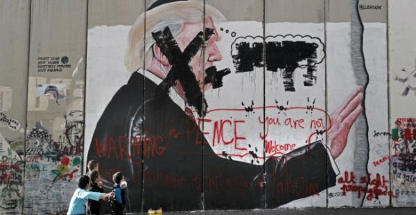© Thomas Coex, AFP | Palestinian children look at vandalised graffiti depicting US President Donald Trump and slogans against the US Vice President painted on Israel's controversial separation barrier in the West Bank city of Bethlehem on December 7, 2017.