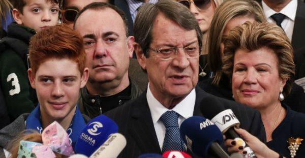 Amir MAKAR / AFP | Cypriot President Nicos Anastasiades (C) stands next to his wife Andri (R) as he addresses the media after casting his vote in the 2018 Cypriot presidential election at a polling station in the city of Limassol on January 28, 2018.
