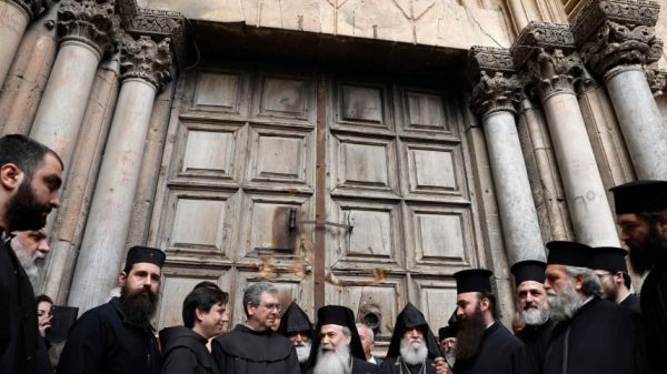 Christian leaders stand outside the closed doors of the Church of the Holy Sepulchre in Jerusalem's Old City, February 25, 2018.GALI TIBBON/AFP