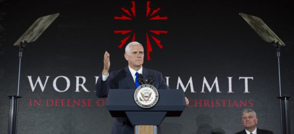 Vice President Mike Pence addresses the World Summit in Defense of Persecuted Christians as Franklin Graham watches, Thursday, May 11, 2017, in Washington. The summit is hosted by Franklin Graham, and the Billy Graham Evangelistic Association. (AP Photo/Cliff Owen)
