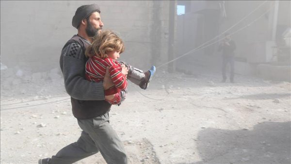 A Syrian man runs with his daughter following air strikes by , Syria by Russian and Syrian Government air forces over residential areas in the de-escalation zone in the Eastern Ghouta region in Damascus (Anadolu Agency)
