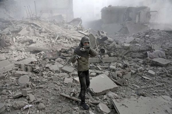 A girl appears from the rubble holding her shoe following an air strike in the besieged rebel-held Eastern Ghouta area near Damascus, Syria, Jan. 9, 2018.