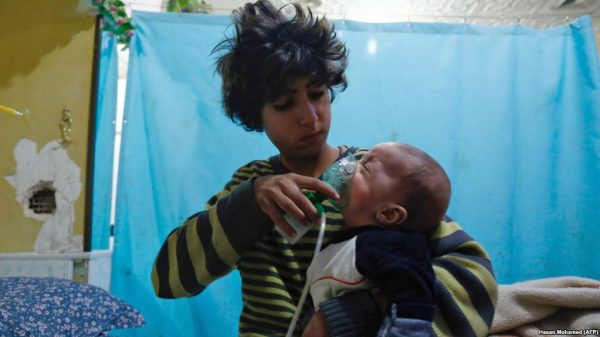 A Syrian boy holds an oxygen mask on an infant at a makeshift hospital after a reported gas attack on the rebel-held town of Douma in the Eastern Ghouta region on the outskirts of Damascus on Jan. 22. (Hasan Mohamed/AFP)