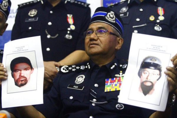 This photo shows Inspector General of Royal Malaysian Police Mohamad Fuzi Harun showing off two images of suspects of killing of a Palestinian scientist Fadi al-Batsh during a press conference in Kuala Lumpur, Malaysia, Monday, April 23, 2018. (AP Photo)