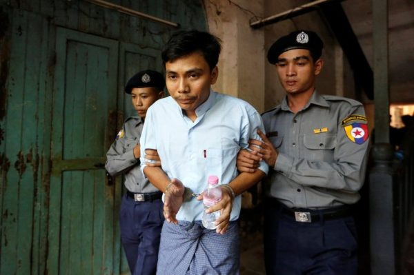 Detained Reuters journalist Kyaw Soe Oo is escorted by police before a court hearing in Yangon, Myanmar April 11, 2018. REUTERS/Ann Wang